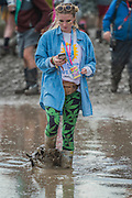Nothing interupts texting. A large puddle left over from teh previous nights rain addsto the problems of moving around  albeit some see it as a leisure facility- 2016 Glastonbury Festival, Worthy Farm, Glastonbury.