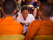 27 FEBRUARY 2015 - PONHEA LEU, KANDAL, CAMBODIA: A woman presents Buddhist monks with rice during a ceremony in her village in Kandal province, Cambodia.    PHOTO BY JACK KURTZ