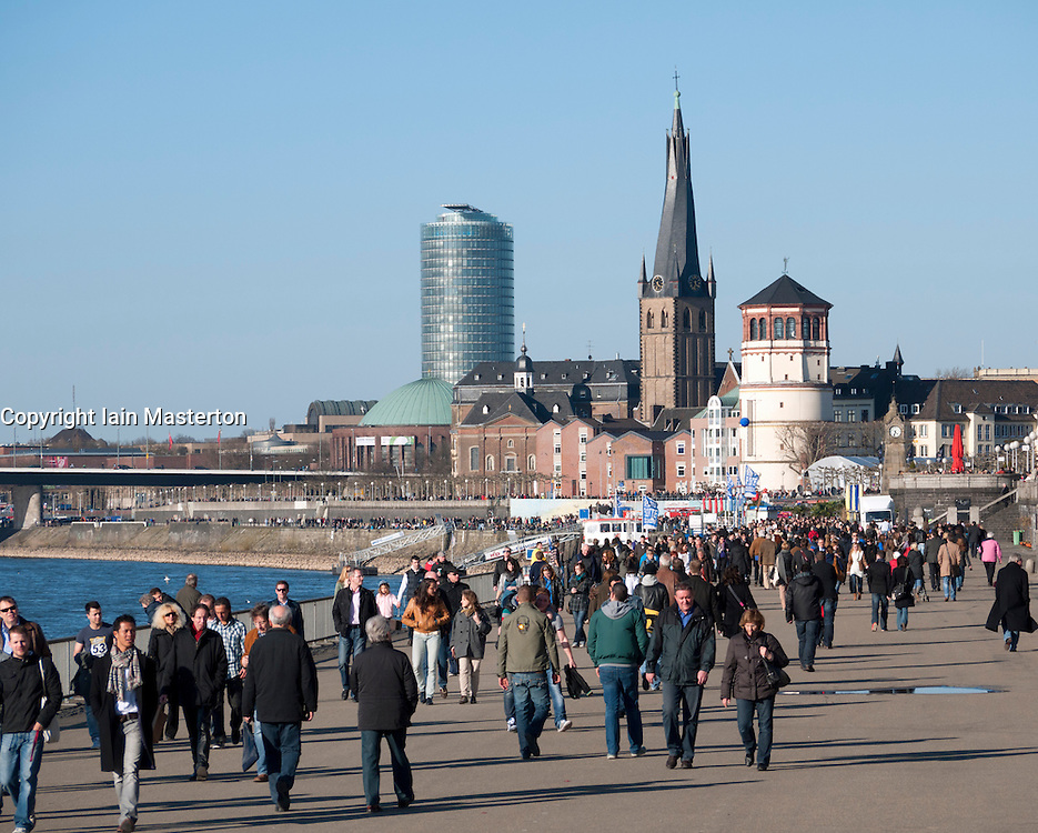 People walking and relaxing beside the River Rhine in Dusseldorf Germany