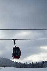 Overhead cable car over snowcapped mountain against cloudy sky