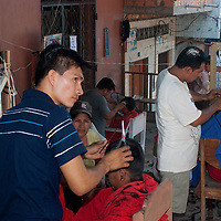 Barbers cut hair in the outdoor market in Belem, a crowded suburb of Iquitos, Peru.