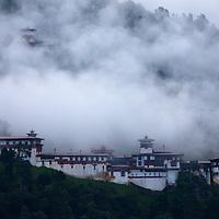 Asia, Bhutan, Trongsa. Trongsa Dzong in clouds, view from Yankhill Resort.