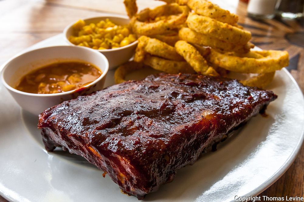 Smoked BBQ ribs on a white plate with onion rings and corn. (Raw file to JPEG)