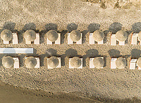 Aerial view of beach with thatch parasols on Santorini island, Greece.