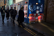 People walk past a hoarding where a footpath is closed in early evening light. East London, UK.