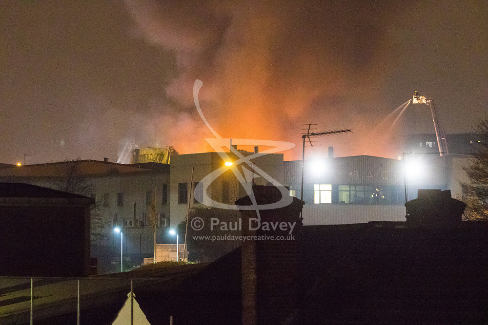 London, January 09 2018. The glow of the fire is seen behind buildings as over 90 Firefighters and 15 fire engines tackle a blaze at a paint factory in Waterloo Road, Staples Corner, west London. © Paul Davey
