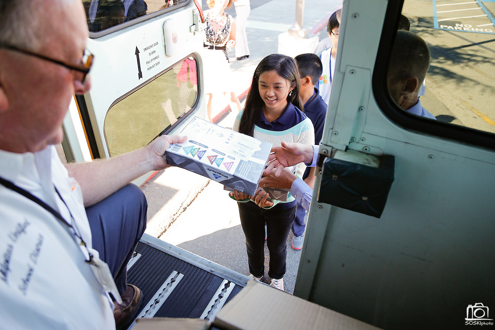 Brian Shreve, MUSD MOT Supervisor, and principal Kristian Lecours hand school supplies to students from a school bus filled with school supplies donated by Wal-Mart at Randall Elementary School in Milpitas, California, on September 5, 2013. (Stan Olszewski/SOSKIphoto)
