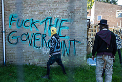 A housing activist stands in front of graffiti at the Sweets Way housing estate on 23rd September 2015 in London, United Kingdom. A group of housing activists calling for better social housing provision in London occupied properties on the 142-home estate in Whetstone, in a few cases refurbishing properties intentionally destroyed by the legal owners following eviction of the original residents, in order to try to prevent the eviction of the last resident on the estate and the planned demolition and redevelopment of the entire estate by Barnet Council and Annington Property Ltd.