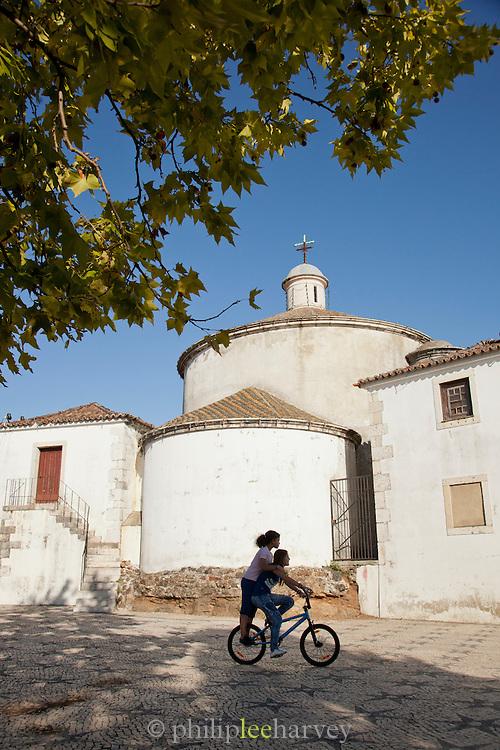 Children play outside the Santo Amaro Chapel in Lisbon, Portugal