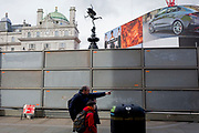 "An adult points out a London site next to a temporary construction hoarding beneath the partially hidden statue of the world famous London Victorian-era landmark, Eros in Piccadilly Circus, on 25th February 2020, in London, England. Eros, or the Shaftesbury Memorial Fountain is located at the southeastern side of Piccadilly Circus in London, United Kingdom. Moved after World War II from its original position in the centre, it was erected in 1892–1893 to commemorate the philanthropic works of Lord Shaftesbury, who was a famous Victorian politician and philanthropist. The monument is surmounted by Alfred Gilbert's winged nude statue generally, though mistakenly, known as Eros. This has been called ""London's most famous work of sculpture."""
