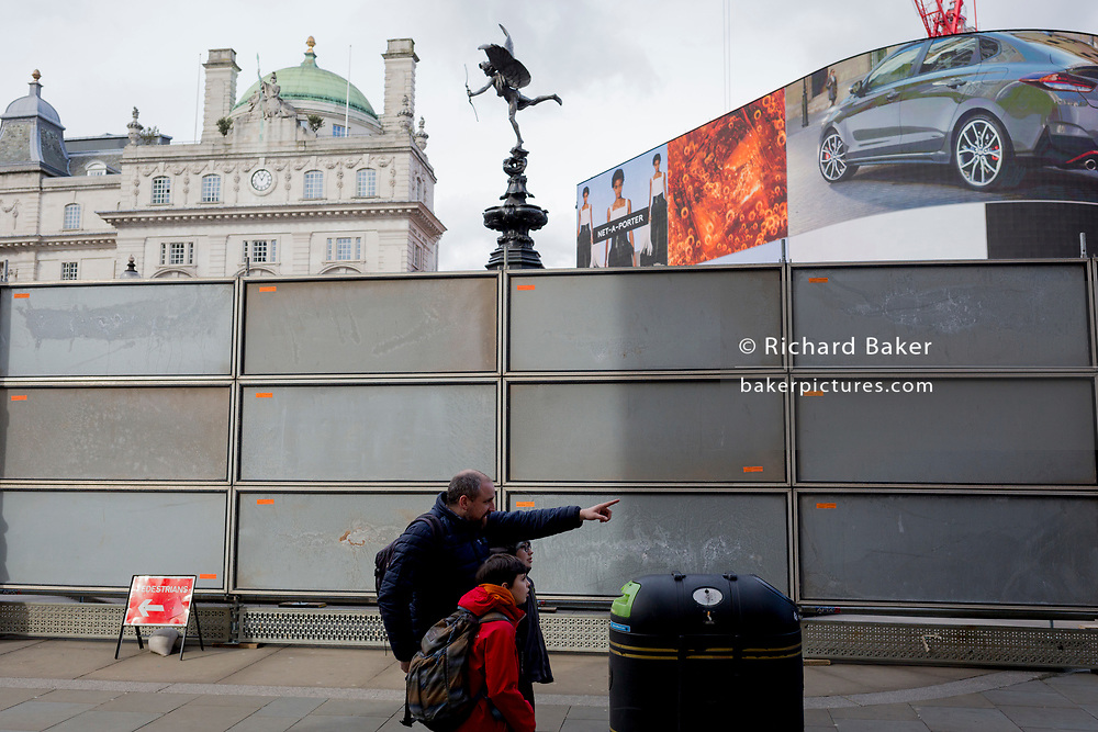 """An adult points out a London site next to a temporary construction hoarding beneath the partially hidden statue of the world famous London Victorian-era landmark, Eros in Piccadilly Circus, on 25th February 2020, in London, England. Eros, or the Shaftesbury Memorial Fountain is located at the southeastern side of Piccadilly Circus in London, United Kingdom. Moved after World War II from its original position in the centre, it was erected in 1892–1893 to commemorate the philanthropic works of Lord Shaftesbury, who was a famous Victorian politician and philanthropist. The monument is surmounted by Alfred Gilbert's winged nude statue generally, though mistakenly, known as Eros. This has been called """"London's most famous work of sculpture."""""""