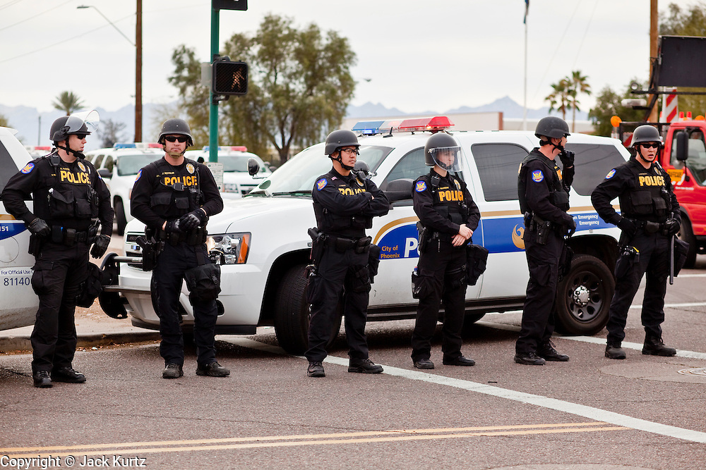 """16 JANUARY 2010 -- PHOENIX, AZ:  Police line up on Durango to keep protestors out of jail and county property during the march against Arpaio. About 10,000 people marched the 2.5 miles from Falcon Park to the """"Tent City"""" on Durango to protest against Maricopa County Sheriff Joe Arpaio and his immigration enforcement tactics.   PHOTO BY JACK KURTZ"""