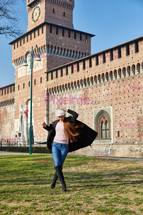 Woman standing in front of Castelo Sforzesco does small victory dance in Milano Italy