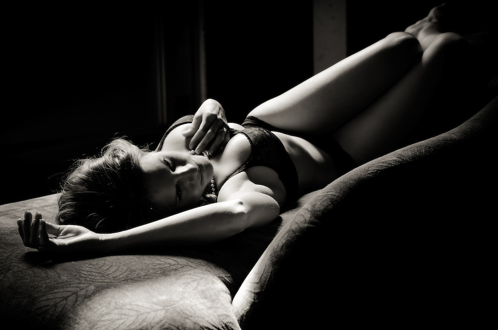 Intimate black and white portrait of woman lying on couch with beautiful lighting at the studio of Kathryn Elsesser Photography.