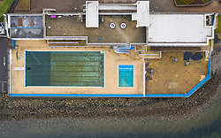 Gourock, Scotland, UK. 9 Mar 2021. Coronavirus lockdown has meant Gourock outdoor swimming pool has been closed to the public for months and the water in the pool has become stagnant and dirty. Much maintenance and cleaning will be required to bring the pool to readiness when lockdown is relaxed.  Pic; Aerial view looking down onto pool area. Iain Masterton/Alamy Live News