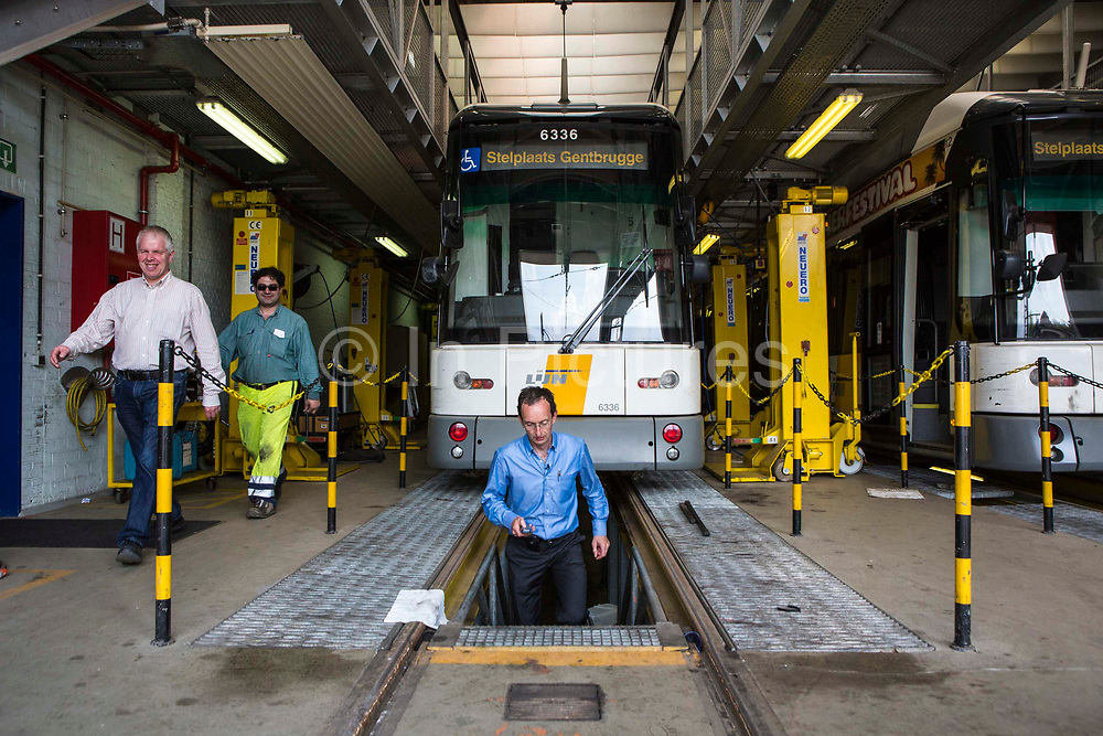 Patrick De Boeuf, Chief Executive of De Lijn, steps up from the pit workshop area beneath a modern tram two males walk along side the tram in the depot in Gentbrugge, Ghent, Belgium.  The trams have been modernized to reduce electricity consumption and won a sustainable travel award from Ashden.