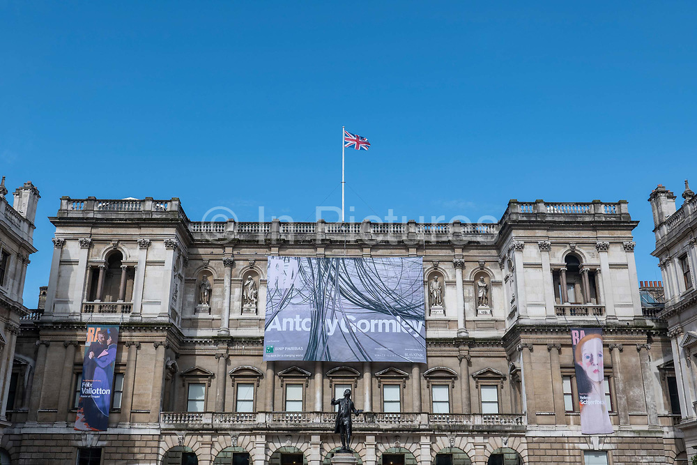 British sculptor, Antony Gormley exhibition promotional display hanging from the exterior building of the Royal Academy of Arts at Burlington House on Piccadilly on the 26th September 2019 in London in the United Kingdom.