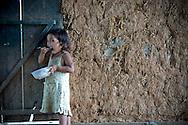 Portraiture of a little girl eating some meal. She stands close to a wattle and daub wall. She belongs to Reungao ethnic tribe. Kontum plateau, Pleiku area, Vietnam, Asia