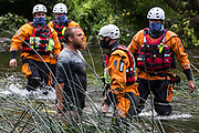 Police officers from Hampshire Police Marine Support Unit move in to detain a male environmental activist from HS2 Rebellion who had been trying to disrupt works to remove an ancient alder tree for the HS2 high-speed rail link on 24th July 2020 in Denham, United Kingdom. A large security operation involving officers from the Metropolitan Police, Thames Valley Police, City of London Police and Hampshire Police as well as the National Eviction Team ensured the removal of the tree by HS2 despite the protests by activists.