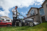 USA, Oregon, Keizer, man mowing his lawn with an electric lawn mower. MR