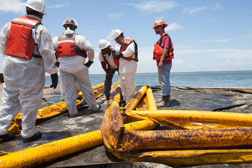 BP clean up crew at a  decontamination area on Grand Isle preparing dirty boom to be cleaned so it can be used again