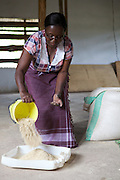 Linna Kinabo mixing the food for her chickens. <br /> <br /> Linna set up and now runs a poultry business selling both eggs and meat.<br /> <br /> She attended MKUBWA enterprise training run by the Tanzania Gatsby Trust in partnership with The Cherie Blair Foundation for Women.