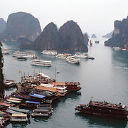 An elevated view of tourist junks visiting Surprise Cave, Ha Long Bay, Vietnam. The bay consists of a dense cluster of 1,969 limestone monolithic islands. Ha Long Bay, is a UNESCO World Heritage Site, and a popular tourist destination. Ha Long, Bay, Vietnam. Photo Tim Clayton