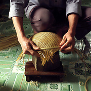 A man shaping a woven bamboo basket in Tang Tien village, Bac Giang province, Vietnam. With Vietnam's growing population making less land available for farmers to work, families unable to sustain themselves are turning to the creation of various products in rural areas.  These 'craft' villages specialise in a single product or activity, anything from palm leaf hats to incense sticks, or from noodle making to snake-catching. Some of these 'craft' villages date back hundreds of years, whilst others are a more recent response to enable rural farmers to earn much needed extra income.