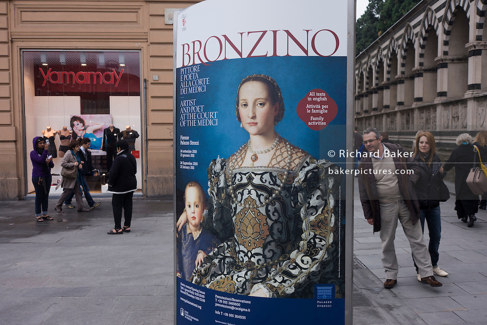 Modern Italian people and Agnolo de Cosimo Bronzino's painting of the Medici Eleanora of Toledo and son Giovanni C1545.The poster advertises the art exhibition by the celebrated painter Agnolo de Cosimo Bronzino. Agnolo de Cosimo Bronzino's painting of the Medici Eleanora of Toledo and son Giovanni C1545. Eleonora di Toledo (1522 - 1562), the daughter of Don Pedro Álvarez de Toledo, the Spanish viceroy of Naples. Eleonora was a patron of the new Jesuit order, and her private chapel in the Palazzo Vecchio  was decorated by Bronzino, who had originally arrived in Florence to provide festive decor for her wedding. She died, with her sons Giovanni and Garzia, in 1562, when she was only forty; all three of them were struck down by malaria while travelling to Pisa.