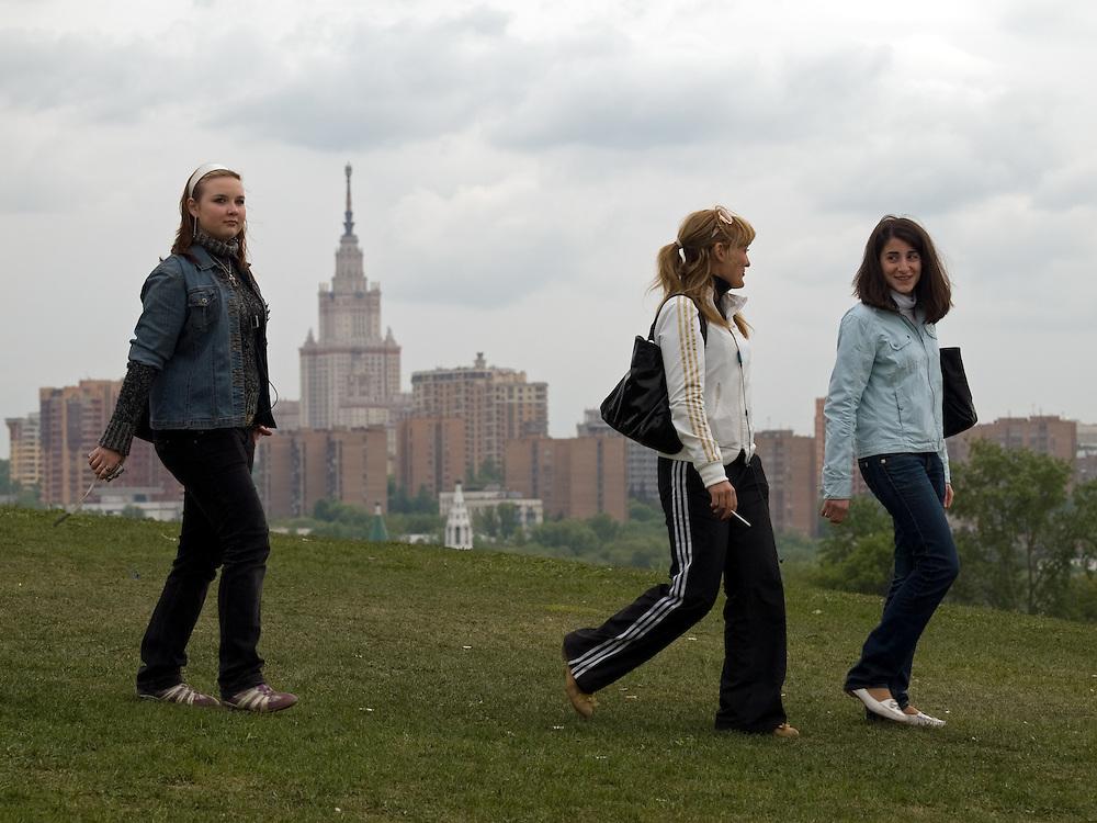 """Drei junge Frauen spazieren über einen Hügel mit dem Namen """"Poklonnaja Gora"""" (Berg der Verbeugungen). Im Hintergrund der Turm des Hauptgebäudes der Lomonossow-Universität in Moskau.<br /> <br /> Three young woman taking a walk across the Poklonnaya Gora hill (Bowing Hill). In the background the tower of Moscows Lomonosov State University."""