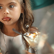 A flower girl is concerned she might get caught in the act after eating too much dessert during a wedding reception on Tybee Island. ©Travis Bell Photography