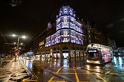 Edinburgh, Scotland, UK. 19 December 2020.  Views of streets and shops in Edinburgh City Centre on evening that Scottish Government announced the highest level 4 lockdown will be enforced from Boxing Day in Scotland.  Pic; Princes Street and Illuminated Jenners Department Store is very quiet at night in the rain. Iain Masterton/Alamy Live News