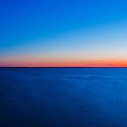 Panorama of the sun setting and the moon rising over Last Mountain Lake, Saskatchewan.
