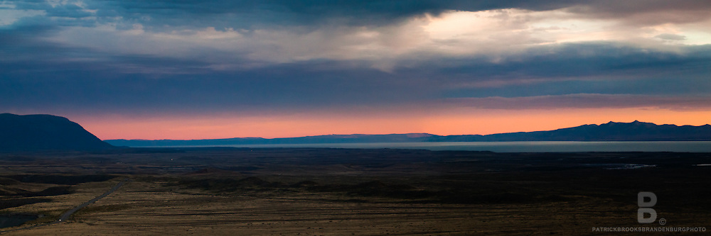 Classic barren road and landscape in a double image panoramic against a bright sunset in Patagonia, Argentina.