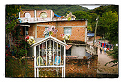 SHOT 2/8/16 4:54:53 PM -  A small roadside capilla in downtown Puerto Vallarta, Mexico. The capilla was dedicated to the memory of a young girl that passed away at the spot that sits along a busy stretch of highway. The capillas are common along the roads and highways of Mexico which is heavily Catholic and are often dedicated to certain patron saints or to the memory of a loved one that has passed away. Often times they contain prayer candles, pictures, personal artifacts or notes. (Photo by Marc Piscotty / © 2016)