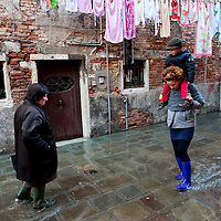 People walks in Central Venice during seasonal High Tide. A few days of exceptional high tides up to 120cm are expected during the next few days..