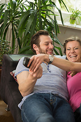 Couple fighting for remote in living room, Munich, Bavaria, Germany