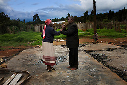 Two people pray on the remains of burnt homes after returning to Morindoko. Four months after post election violence caused 300,000 Kenyans to leave their homes, the long process to resettle has begun. In Molo, a town in Kenya's Rift Valley where most of the violence occured, thousands of people returned to their homes with little or nothing to build upon.  .
