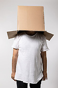 Man with box on his head, concept and madness. Copy space