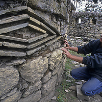 Peruvian archaeologist Dr. Peter Lerche examines ancient patterns he believes to symbolize eyes that are built into many walls at Kuelap, a stronghold of the pre-Incan Chachapoyan culture.