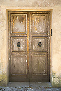 Quaint old weather-beaten wooden double door and doorway in historic centre of Erice, Sicily, Italy