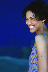 african american woman looking off smiling while standing against a bright blue background