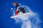 Teen snowboarder fly through the air.