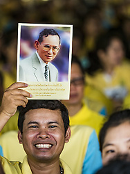 June 9, 2016 - Bangkok, Bangkok, Thailand - A man holds a picture of Bhumibol Adulyadej, the King of Thailand, over his head during a prayer after the merit making ceremony at the Grand Palace. Thailand marked 70 years of the reign of Bhumibol Adulyadej, with a special alms giving ceremony for 770 monks in front of the Grand Palace in Bangkok. The King, also known as Rama IX, ascended the throne on 9 June 1946. He is the longest serving monarch in Thai history and the longest serving monarch in the world today. He is revered by most Thais and is widely seen as a unifying figure in the country. (Credit Image: © Jack Kurtz via ZUMA Wire)