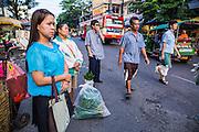 19 OCTOBER 2012 - BANGKOK, THAILAND:   Commuters wait for a city bus in the Bangkok Flower Market.   PHOTO BY JACK KURTZ