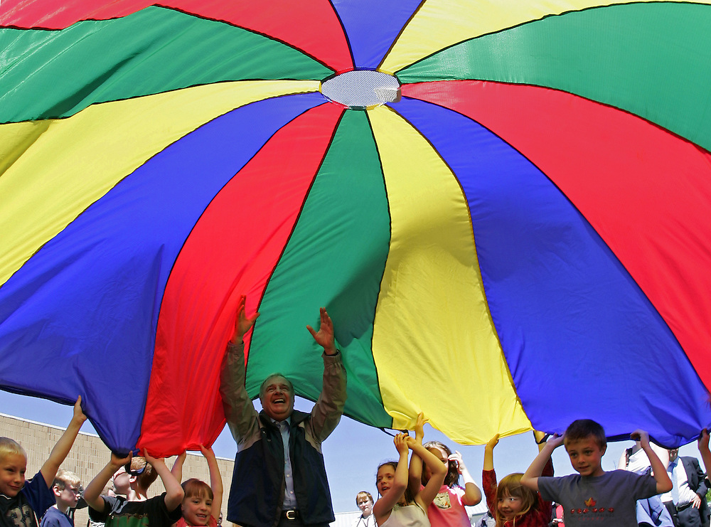 Canadian Prime Minister Paul Martin (C) plays with children under a color canopy at a school in Regina, Saskatchewan, June 23, 2004. REUTERS/Jim Young
