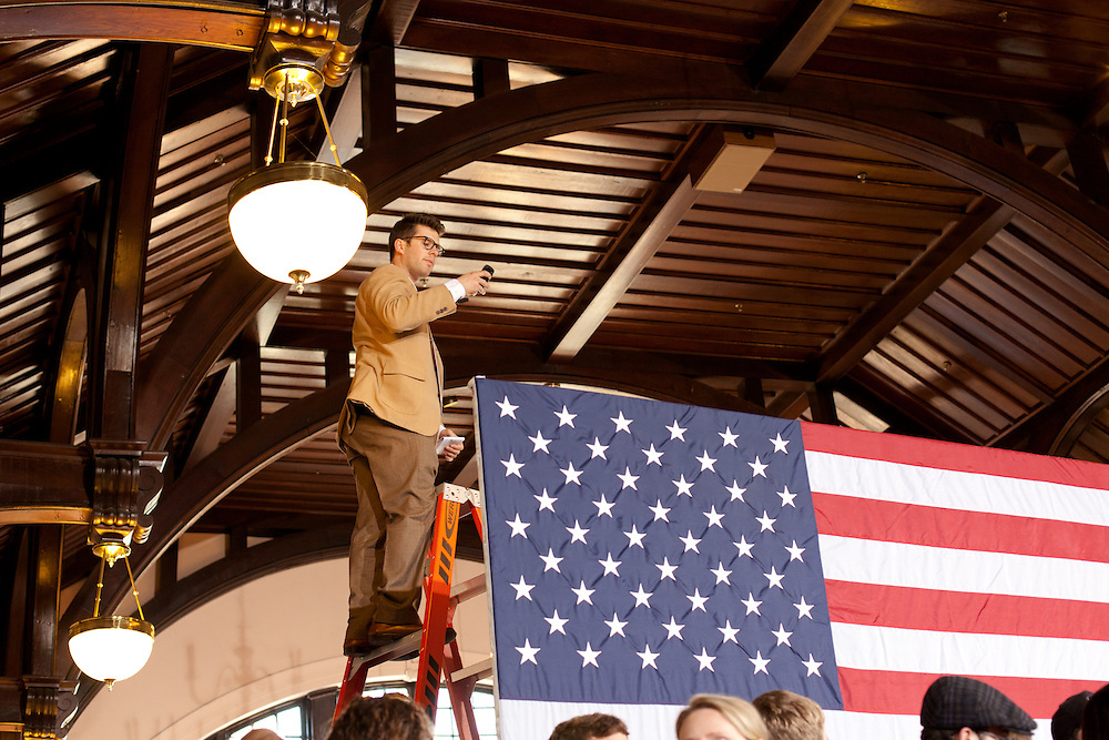 An aid to the Mitt Romney campaign stands on a ladder to get a better view of the crowd.