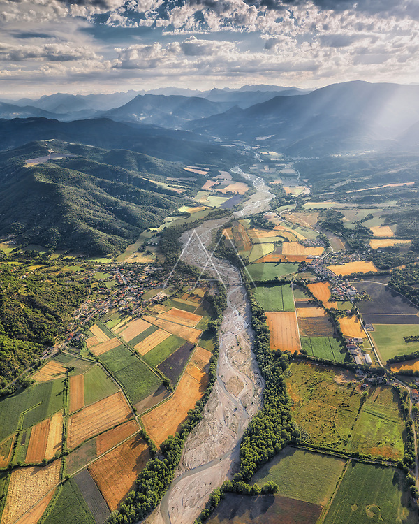 Aerial view of dry river with lavender fields around with mountains in background in Bras-d'Asse, Alpes-de-Haute-Provence, France.