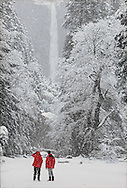 Visitors to Yosemite National Park during winter admire Lower Yosemite Falls while on a short hike in the valley.