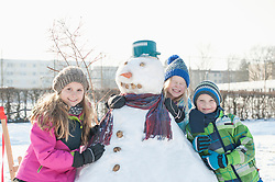 Portrait of children leaning on snowman